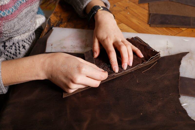 En muchacha del taller las manos hacen el monedero imagen de archivo libre de regalías