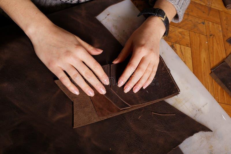 En muchacha del taller las manos hacen el monedero imágenes de archivo libres de regalías