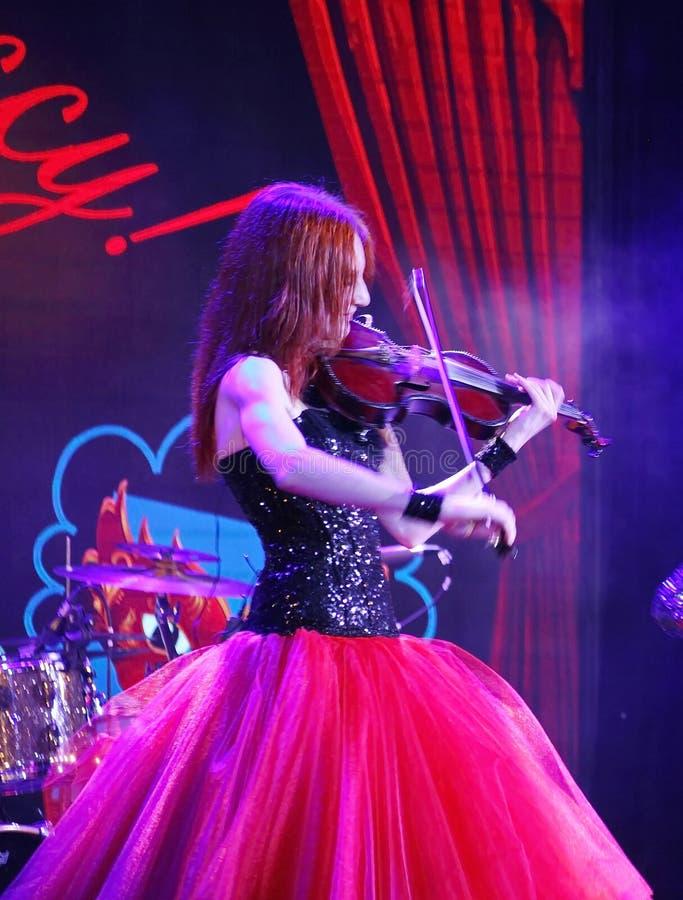 En muchacha hermosa, frágil y delgada de la etapa - con el pelo rojo ardiente - un músico bien conocido, violinista Maria Bessono imagenes de archivo