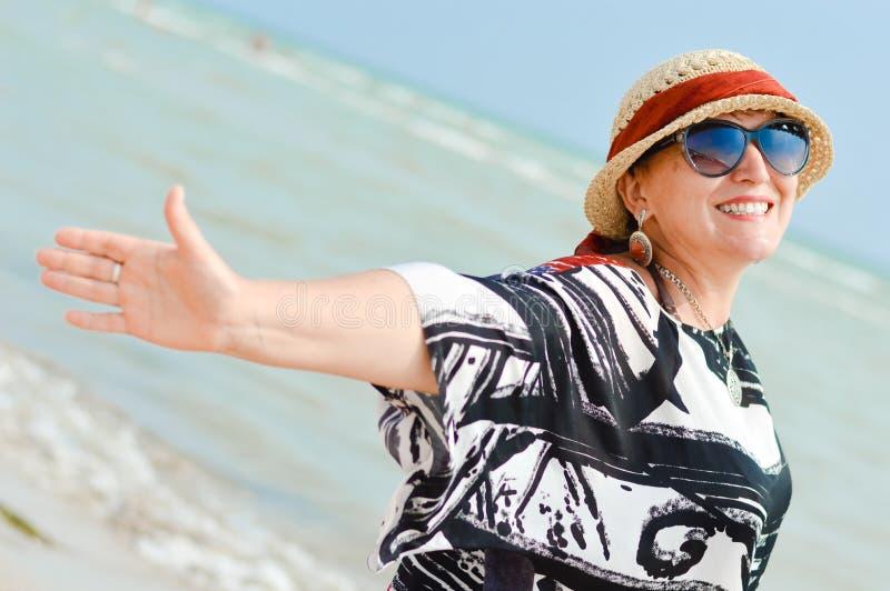 En mujer madura sonriente y de mirada feliz de la cámara que goza de la brisa en la costa imágenes de archivo libres de regalías