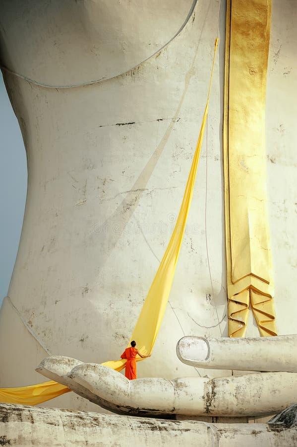 En munk som förbereder den gula ämbetsdräkten för Buddhastaty arkivbild