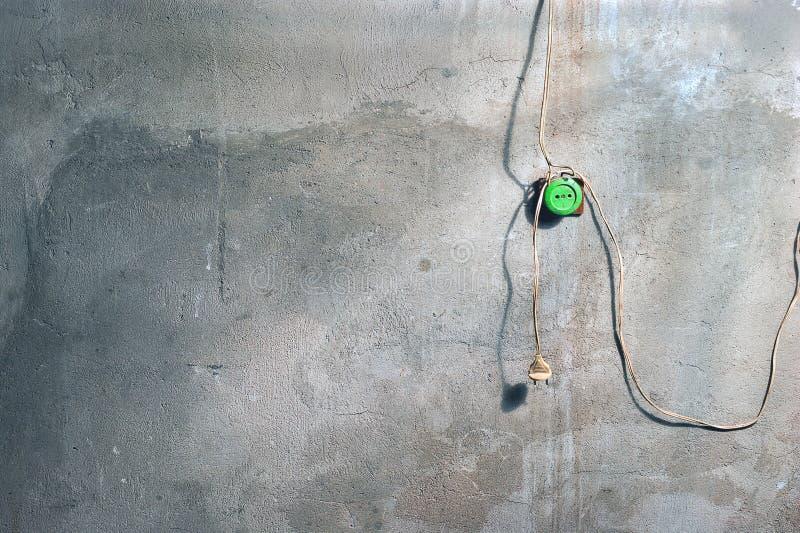 En murbrukvägg med sprickor och målarfärgfläckar i seminariet med den gamla gröna håligheten för elektrisk propp och hängande trå royaltyfria foton