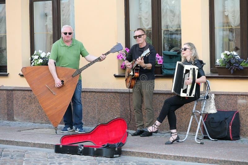 En musikalisk grupp av tre personer p? en gammal europeisk gata Musikbandet best?r av tv? m?n och en flicka M?n med en basfiol oc royaltyfri fotografi