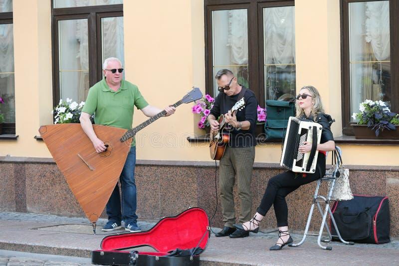En musikalisk grupp av tre personer p? en gammal europeisk gata Musikbandet best?r av tv? m?n och en flicka M?n med en basfiol oc fotografering för bildbyråer