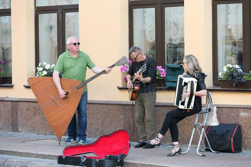 En musikalisk grupp av tre personer p? en gammal europeisk gata Musikbandet best?r av tv? m?n och en flicka M?n med en basfiol oc arkivfoto