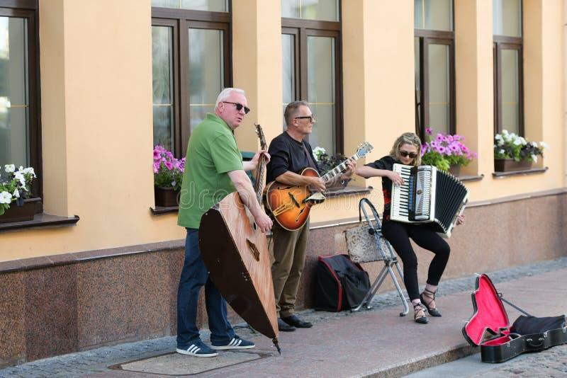 En musikalisk grupp av tre personer p? en gammal europeisk gata Musikbandet best?r av tv? m?n och en flicka M?n med en basfiol oc royaltyfria bilder