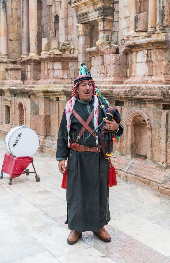 En musiker i nationell kläder spelar det säckpipe- och poserar med en turist i sydlig teater fördärvar in av den romerska staden  fotografering för bildbyråer