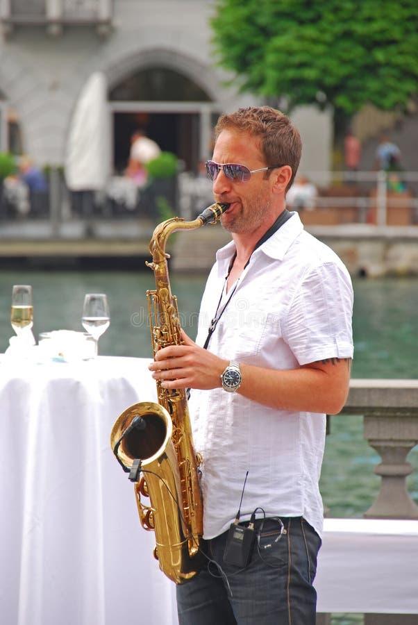 En musiker som spelar saxofonen på gatan bredvid den Reuss floden på Lucerne arkivfoton