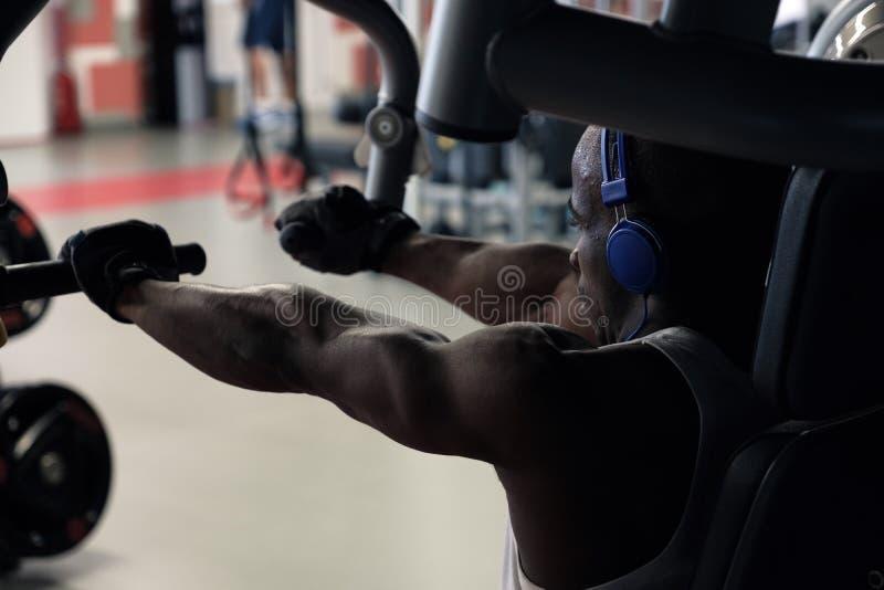 En muskulös man är förlovad på simulatorn, en betoning på händerna royaltyfri foto
