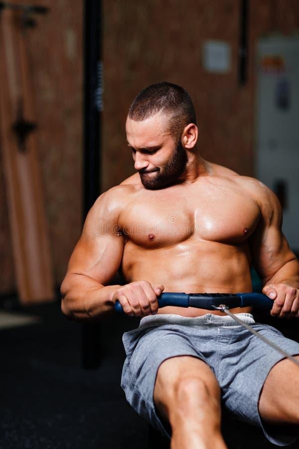 En muskulös vuxen man som gör övningar på en simulator på en idrottshallbakgrund Kondition, sportar och sunt livsstilbegrepp royaltyfri fotografi