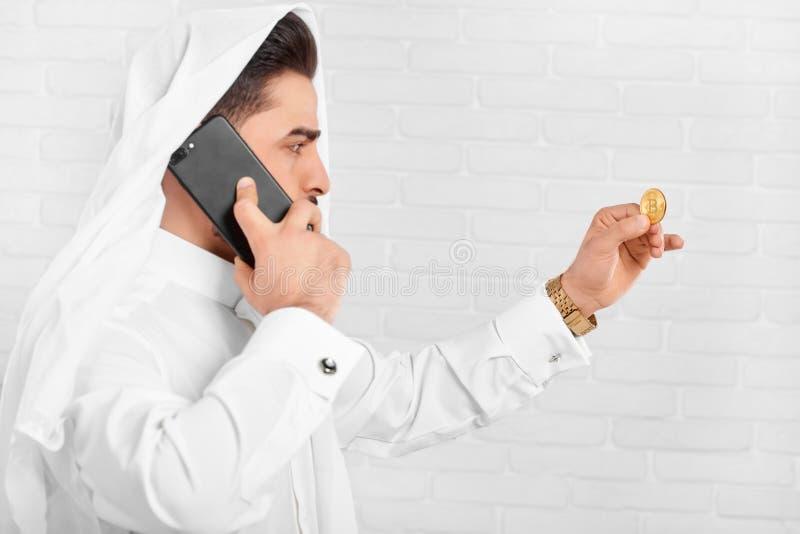 En muslimsk affärsman i traditionell dräkt ser på guld- bitcoin arkivbilder