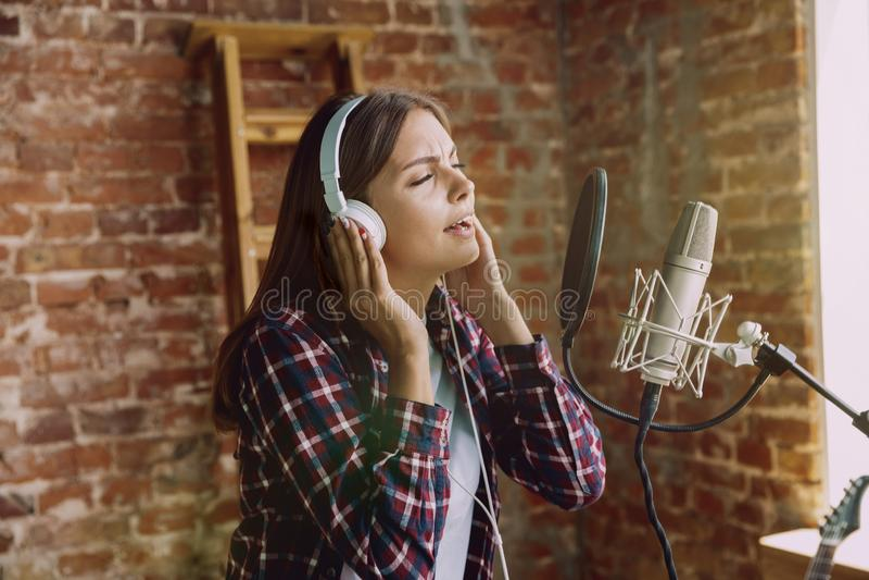 En muziek die van de vrouwenopname, die thuis uitzenden de zingen stock afbeelding