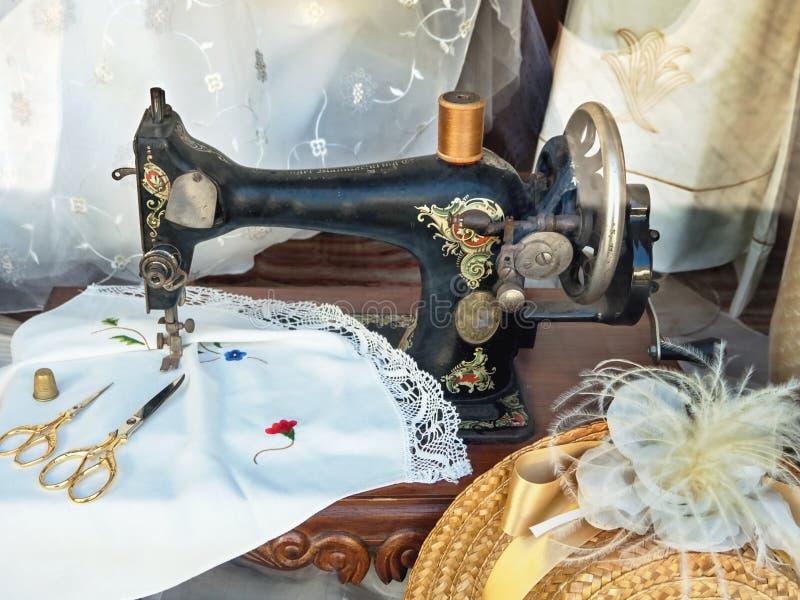 En mycket gammal pedalsymaskin i svart med dekoren som omges, genom att sy redskap royaltyfria bilder