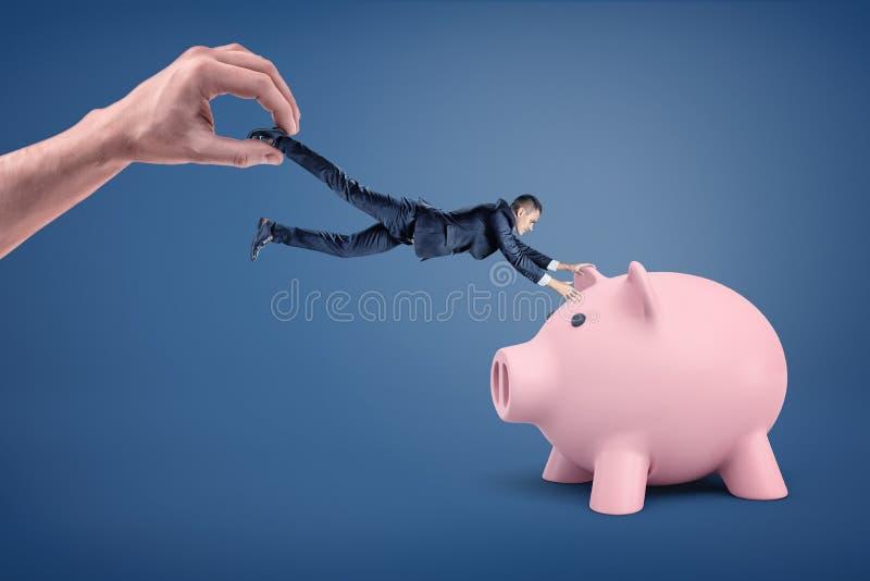 En mycket liten affärsman försöker att gripa på en stor spargris, men han släpade bort vid en jätte- hand arkivfoto