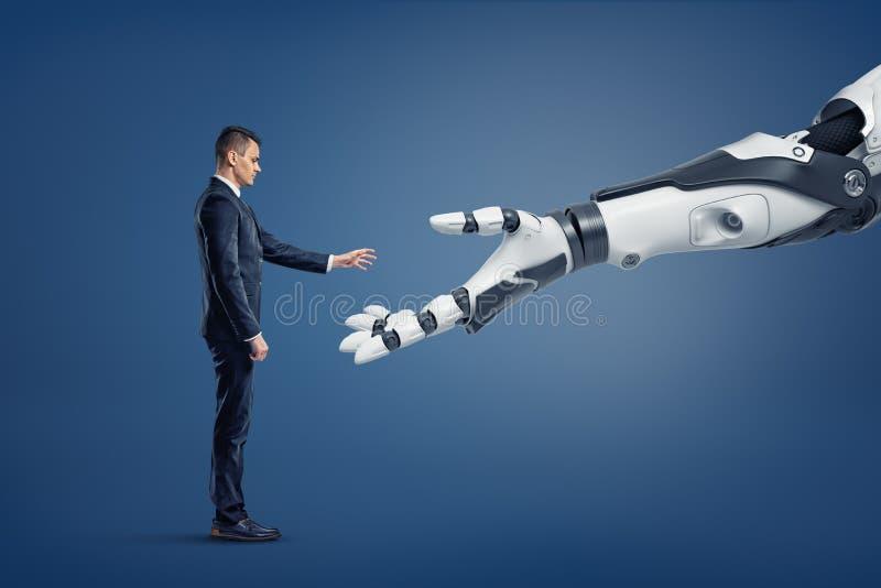 En mycket liten affärsman står i en sidosikt och lyfter hans hand för att trycka på en jätte- robotic arm royaltyfria bilder