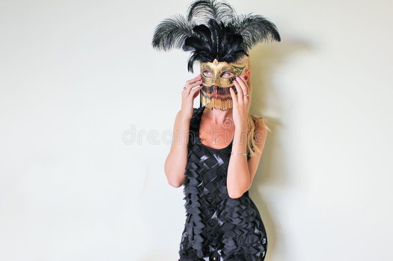En mystisk främling i den Venetian maskeringen som dekoreras med guld och fjädrar royaltyfri bild