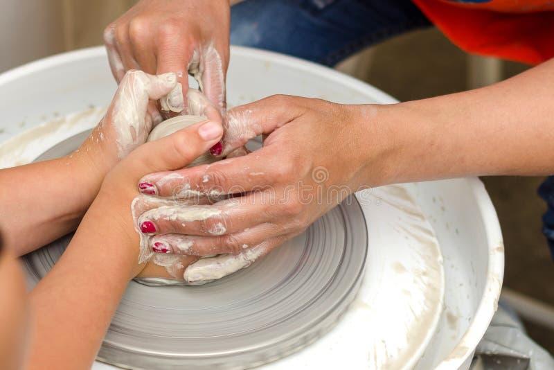 En närbild av barnet lär att knåda leran fotografering för bildbyråer