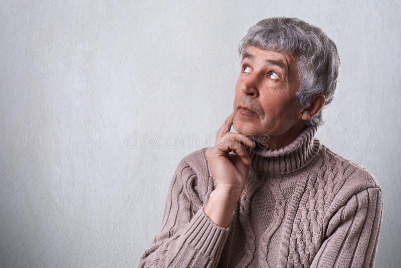 En närbild av det drömlika äldre manliga innehavet hans hand under hakan som ser ha åt sidan fundersamt faraway uttryck Mogen man arkivfoton