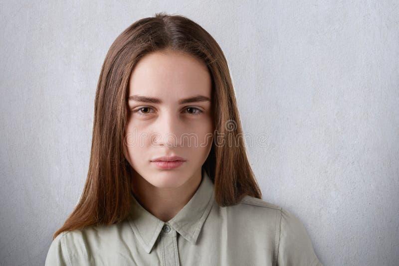 En närbild av en härlig ung flicka med skinande ögon och rakt långt mörkt hår som har en mörk framsida som ser rak i caen royaltyfri fotografi