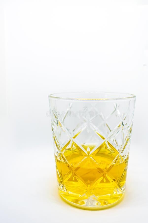 En närbild av ett exponeringsglas av wiskey som isoleras på en vit bakgrund arkivfoto