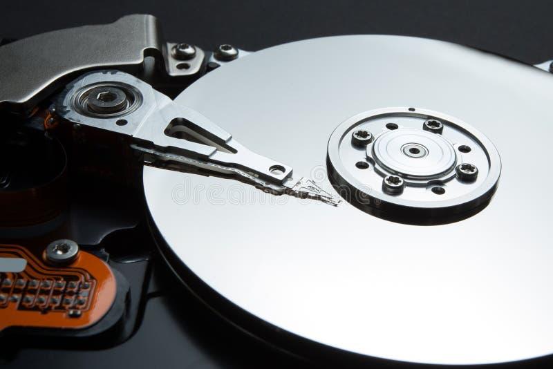 En närbild av en magnetisk skiva och ett läs- huvud på en svart bakgrund Personliga data för återställande av användare på hårddi arkivbild