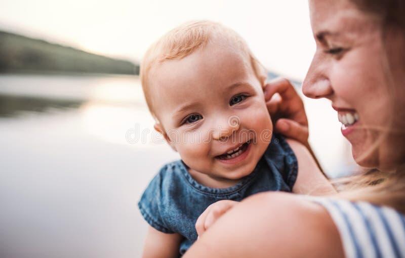 En närbild av modern med en litet barndotter utomhus vid floden i sommar arkivbilder
