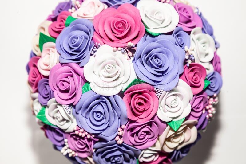 En närbild av en romantisk konstgjord bukett av blommor av ett lila, rosa och vitt tyg som göras från foamiran på en tom bakgrund fotografering för bildbyråer