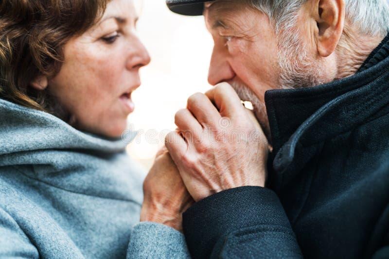 En närbild av stående det fria för höga par som värmer händer upp när förkylning arkivbilder