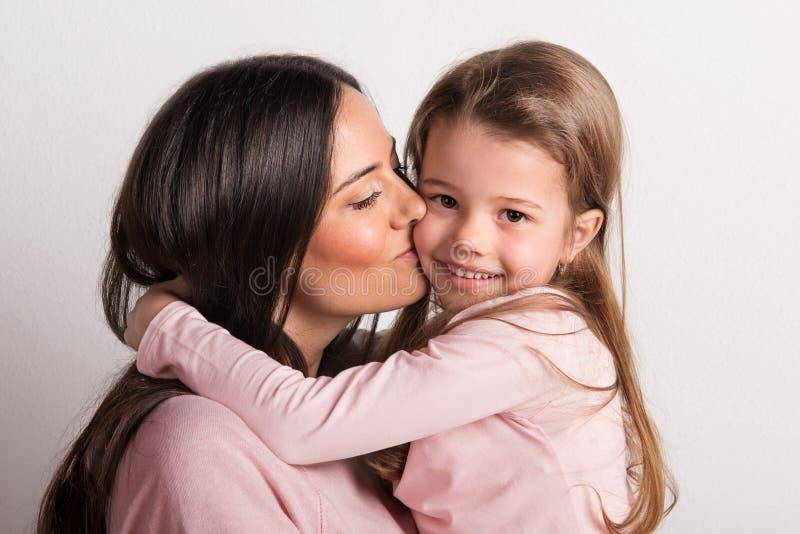En närbild av en ung moder som kysser hennes lilla dotter i en studio arkivbild