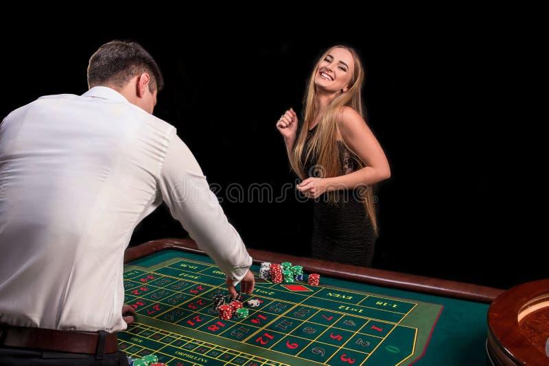 En närbild på baksidan av croupier i en vit skjorta, bilden av den gröna kasinotabellen med rouletten och chiper, rich royaltyfri bild