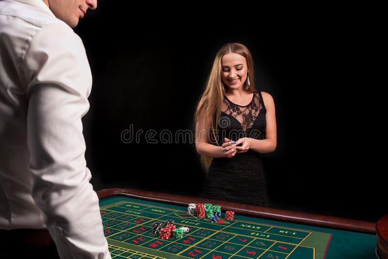 En närbild på baksidan av croupier i en vit skjorta, bilden av den gröna kasinotabellen med rouletten och chiper, rich royaltyfri foto