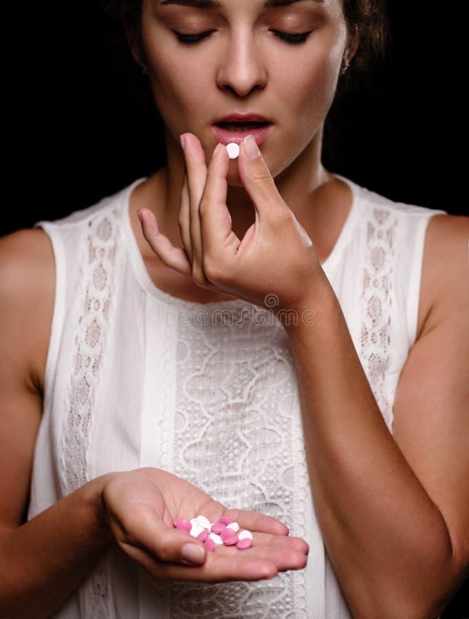 En närbild sköt av en ung kvinna som tar minnestavlor En hög av preventivpillerar i en kvinnlig hand på en svart bakgrund Medicin arkivfoton