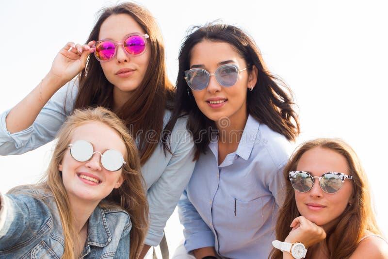 En närbildselfie av de fyra härliga brudtärnorna i färgrik solglasögon på bakgrunden av himlen royaltyfria foton
