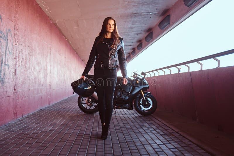 En nästa superbike för härlig hjälm för cyklistflickainnehav går på en trottoar inom bron fotografering för bildbyråer