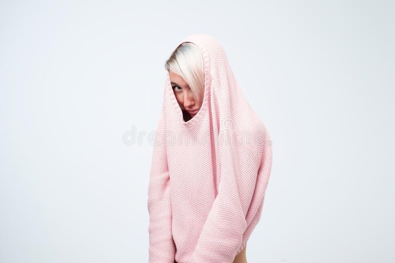 En nätt caucasian flicka med en social fobi döljer hennes framsida i en tröja royaltyfria foton