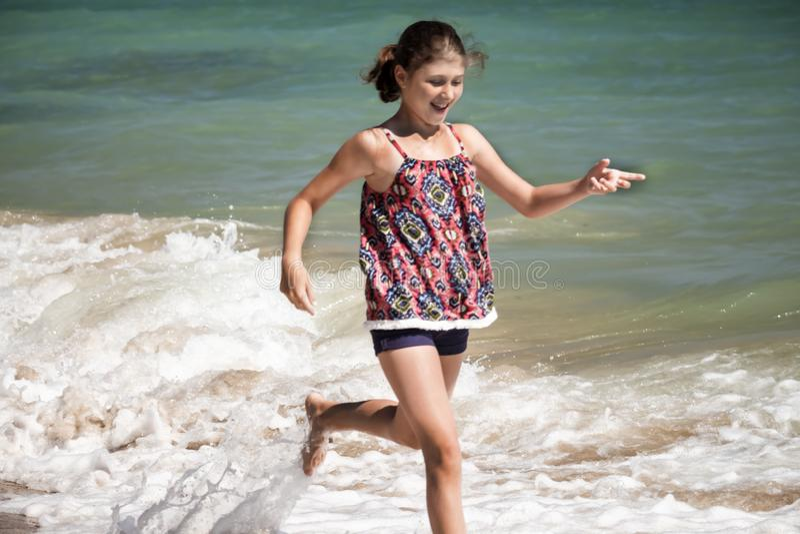 En nätt flicka som kör i vågorna på stranden som göras suddig, sommarbegrepp arkivfoton
