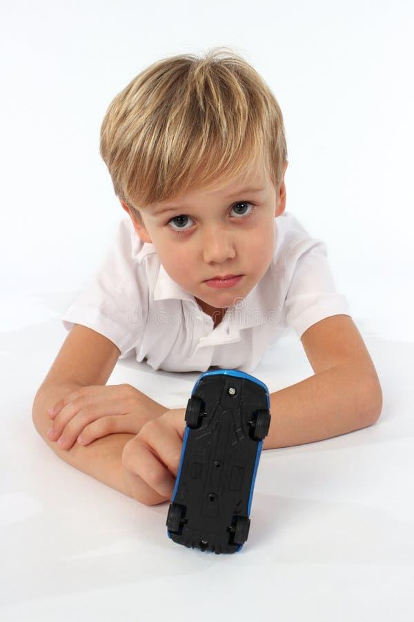 En nätt ganska hårbarnpojke som spelar med en billeksak fotografering för bildbyråer