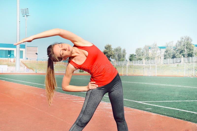 En nätt kvinnaidrottsman nen som sträcker hennes kropp på stadionspåret royaltyfri bild