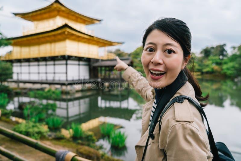 En nätt kvinnlig handelsresande som pekar till templet fotografering för bildbyråer
