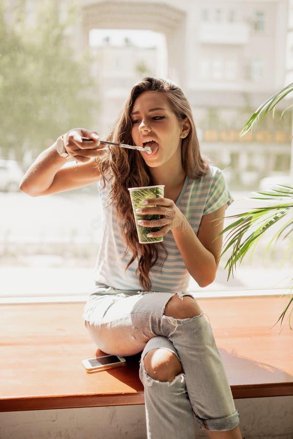 En nätt slank ung flicka med långt hår, bärande tillfällig dräkt, sitter på fönsterbrädan och dricker kaffe i ett hemtrevligt kaf arkivfoto