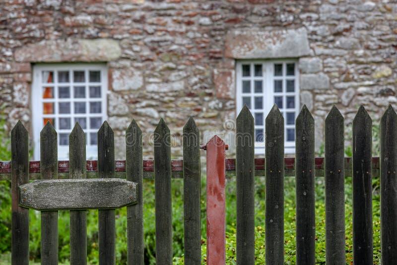 En nätt stenstuga med stenöverstycken och vita spröjsade fönsterställningar som omges av gräs och ett posteringstaket arkivbilder