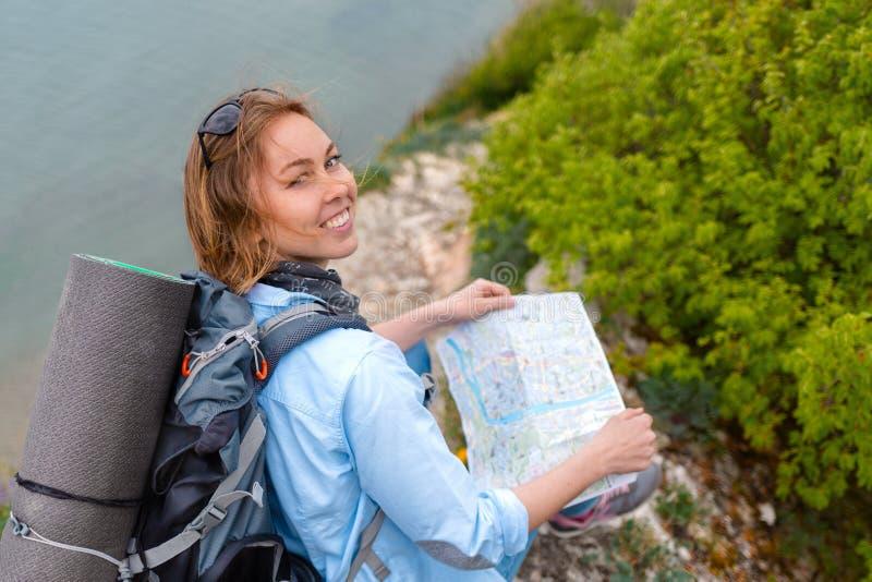 En nätt turist- kvinna sitter på en stenbergbana med en översikt i hennes händer Fotvandra och sportar close upp royaltyfri bild