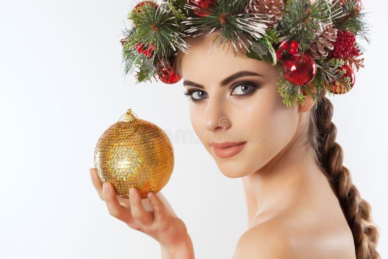 En nätt ung kvinna rymmer i hennes hand en guld- julboll, på hennes huvud en härlig krans av granen med kottar och bollar royaltyfri fotografi