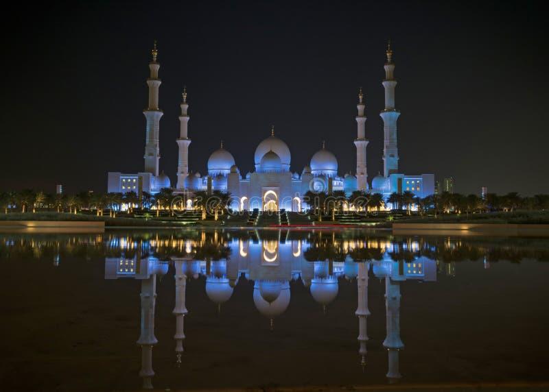 En nattsikt av Sheikh Zayed Grand Mosque från en vattenreflexion arkivbilder
