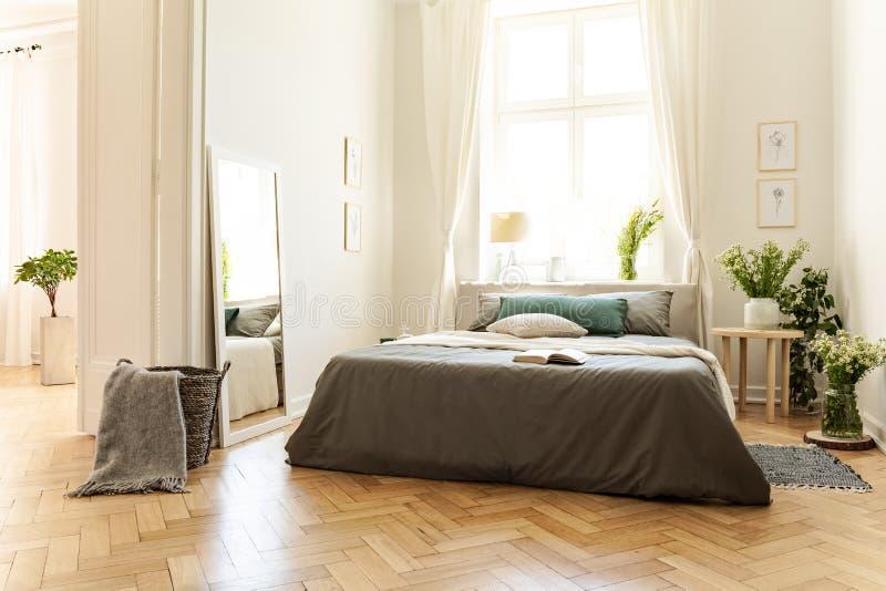 En naturlig ljus lägenhetinre med trägolvet, vita väggar och soliga fönster En säng med grå linne och ny ängflowe arkivbilder