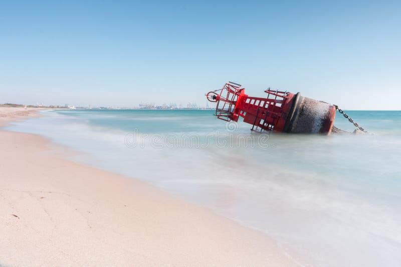 En navigeringboj som strandas p? stranden av de starka str?mmarna av en storm med en l?ng utl?ggning f?r en siden- effekt royaltyfria bilder