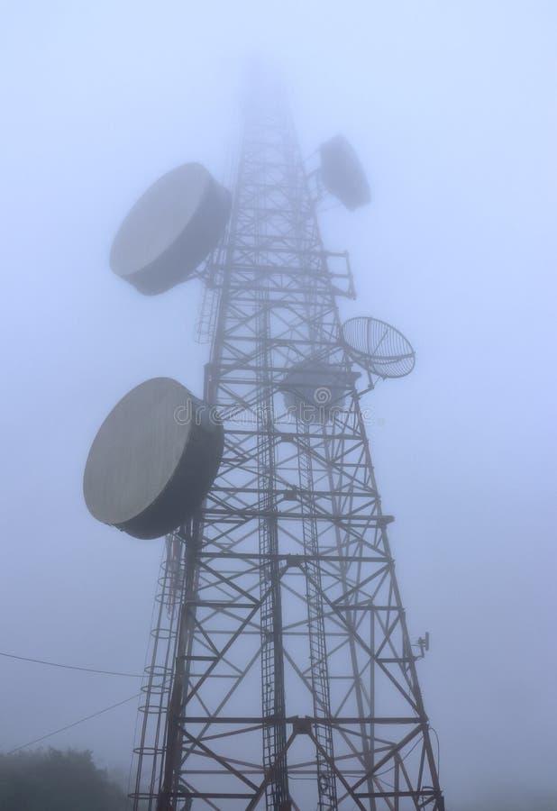 En nedersta sikt av ett radiotorn i en dimma royaltyfri fotografi