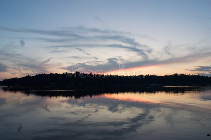 En nedgångsolnedgång vänder en sjö in i en spegel arkivfoto