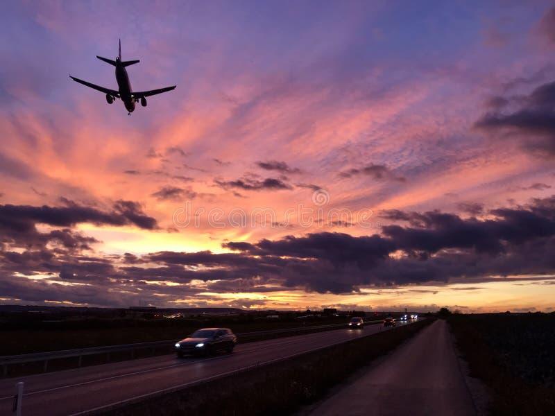 En nivå att närma sig den Stuttgart flygplatsen under en dramatisk solnedgång arkivfoton