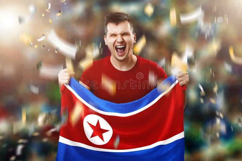 En nordkoreansk fan, en fan av en man som rymmer nationsflaggan av Nordkorea i hans händer Fotbollfan i stadion Blandat massmedia royaltyfria foton